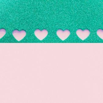 Papel com pequenos corações cortados na mesa roxa