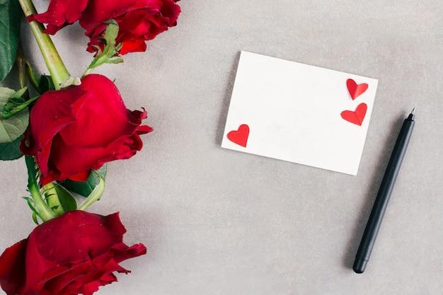 Papel com pequenos corações perto de caneta e flores