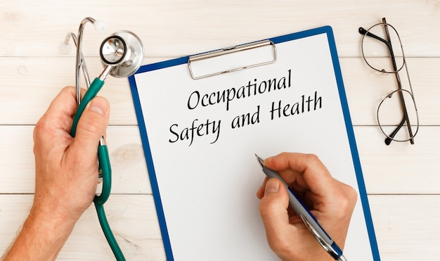 Papel com segurança e saúde ocupacional na mesa do escritório, estetoscópio