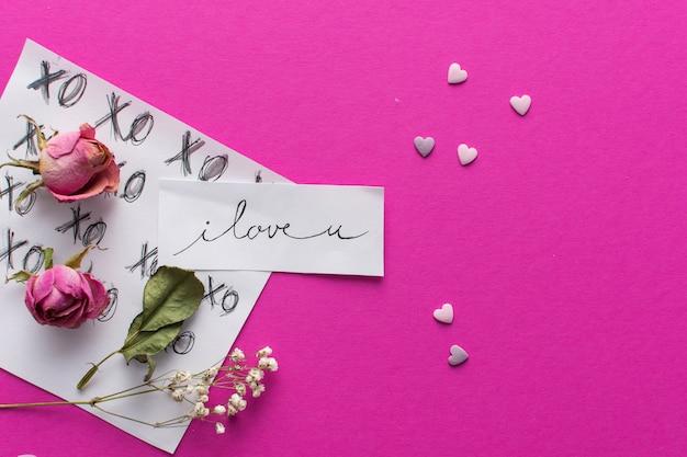 Papel com título perto de corações de ornamento e conjunto de flores