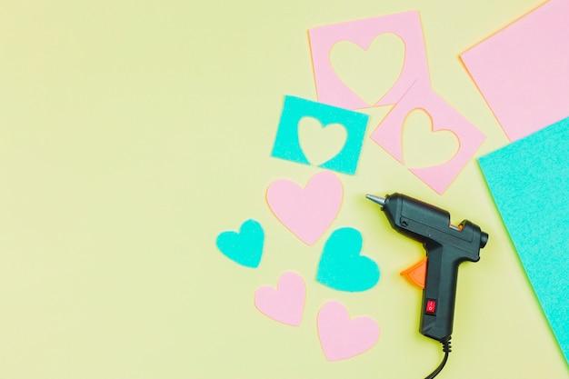 Papel cortado em forma de coração e pistola de cola no pano de fundo amarelo