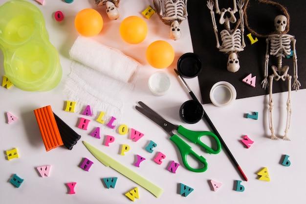 Papel, curativo, plasticina com tintas sobre uma mesa de madeira. aranha de cartão de saudação de halloween e teia de aranha, esqueletos de fantasmas. artesanato para crianças