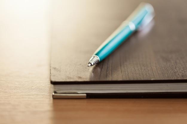 Papel de anotações em branco com caneta sobre fundo de madeira