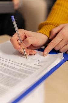 Papel de assinatura de empresária, mão do parceiro firma documento comercial fazendo acordo de contrato de trabalho, conceito de seguro de empréstimo bancário, registro de certificado de patente, vista de perto