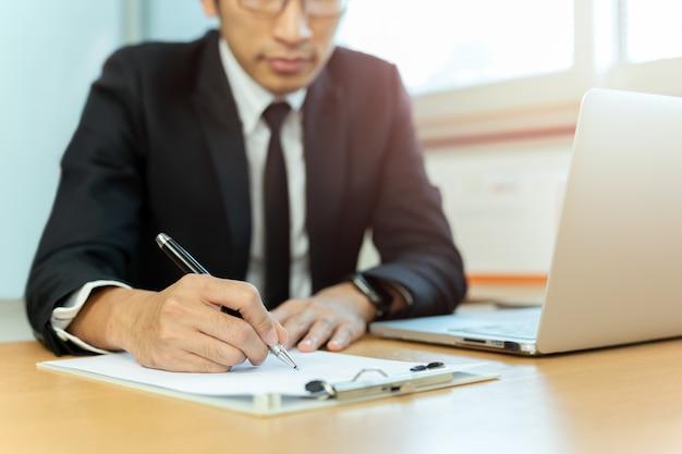 Papel de assinatura do contrato do homem de negócios com pena e portátil na mesa de escritório.