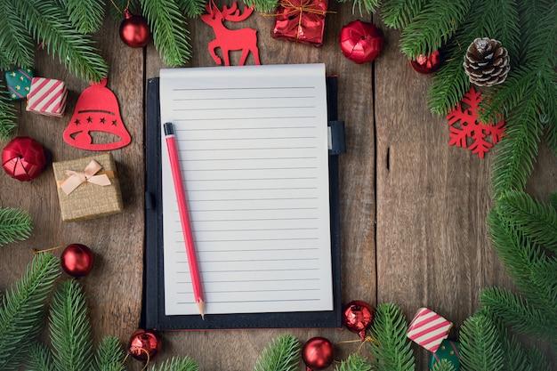 Papel de bloco de notas de tela em branco com fundo de natal com enfeites na placa de madeira.