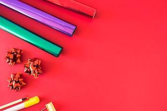 Papel de brilho com conjunto de arco e papelaria no fundo