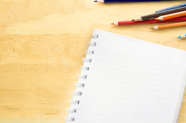 Papel de caderno de vista superior. lápis de cor coloridos na mesa de madeira.