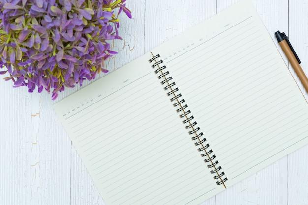 Papel de caderno em branco e caneta na madeira,