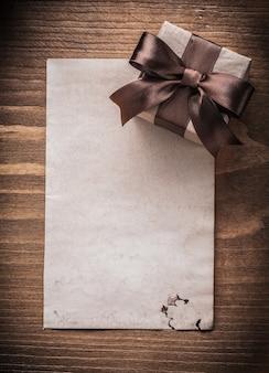 Papel de caixa de presente embrulhado no conceito de férias em placa de madeira vintage