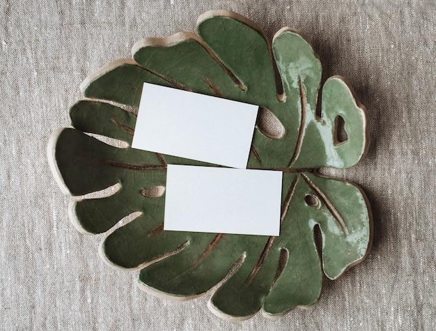 Papel de carta de verão natureza morta maquete de cartão de visita em branco na placa de cerâmica da folha de monstera