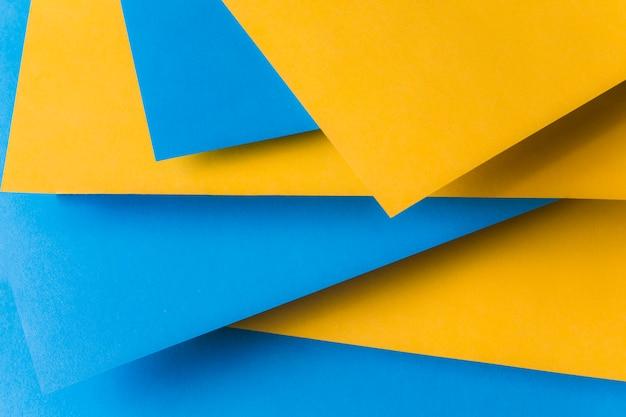 Papel de cartão amarelo e azul em camadas sobre outro