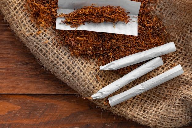 Papel de cigarro e pilha de tabaco na mesa de madeira