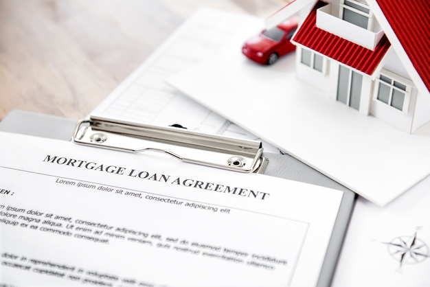 Papel de contrato de empréstimo hipotecário imobiliário com modelo de casa em cima da mesa