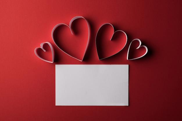 Papel de coração vermelho e em branco com o cartão de nota sobre fundo vermelho