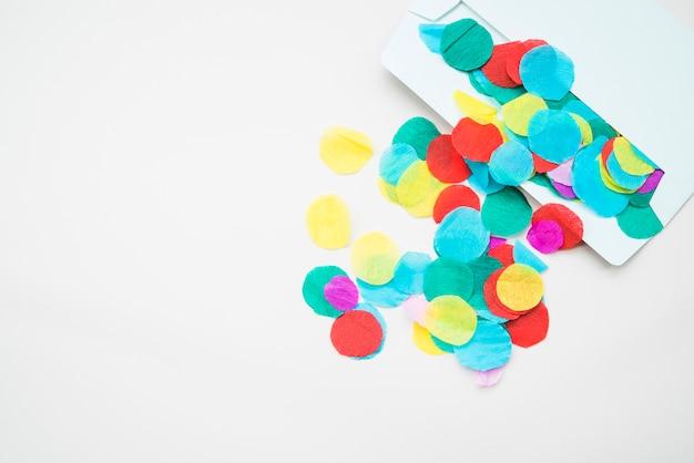 Papel de crepe colorido de um envelope aberto contra um fundo branco