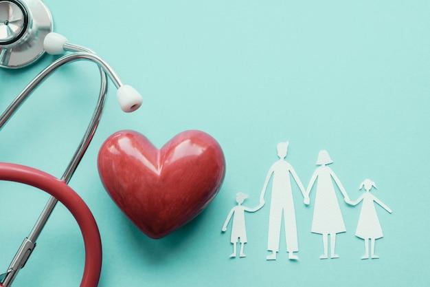 Papel de família cortado com coração vermelho e estetoscópio, saúde do coração, conceito de seguro de saúde familiar