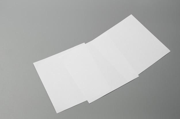 Papel de mock-up do retrato em branco. revista brochura isolada em cinza, fundo mutável