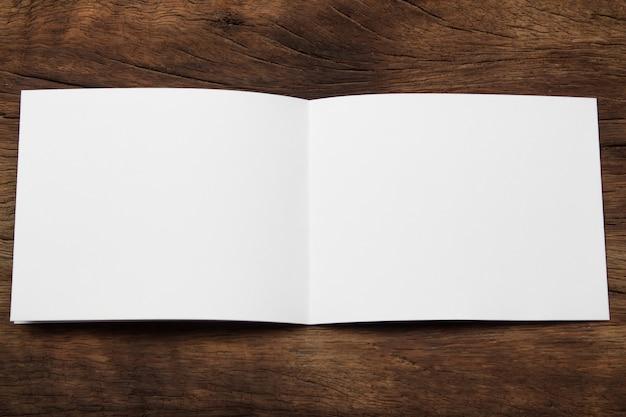 Papel de mock-up do retrato em branco. revista brochura isolada na mesa de madeira marrom