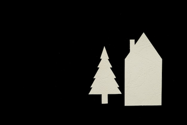 Papel de natal e casa cortado sobre fundo preto