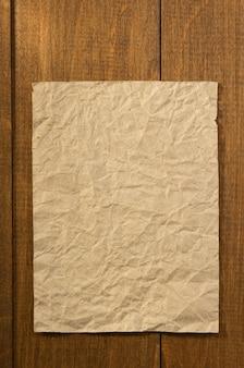 Papel de nota amassado em fundo de madeira