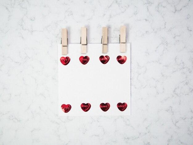 Papel de nota com prendedor de roupa de madeira e objetos em forma de coração no fundo de mármore, feliz dia dos namorados, dia das mães, lay-out, vista superior