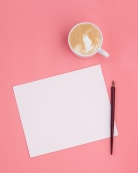 Papel de nota com xícara de café e caneta de tinta no fundo rosa