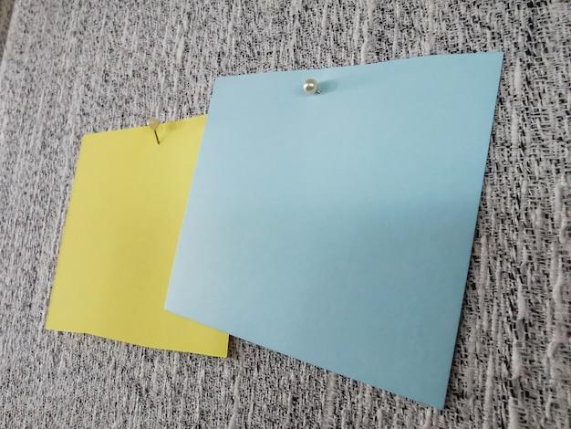 Papel de nota de close-up e muitas cores pushpin em placa cinza