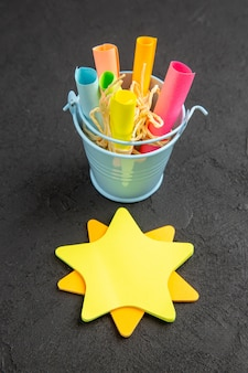 Papel de nota de estrela de vista inferior enrolado em notas auto-adesivas amarradas com corda em um pequeno balde na mesa preta