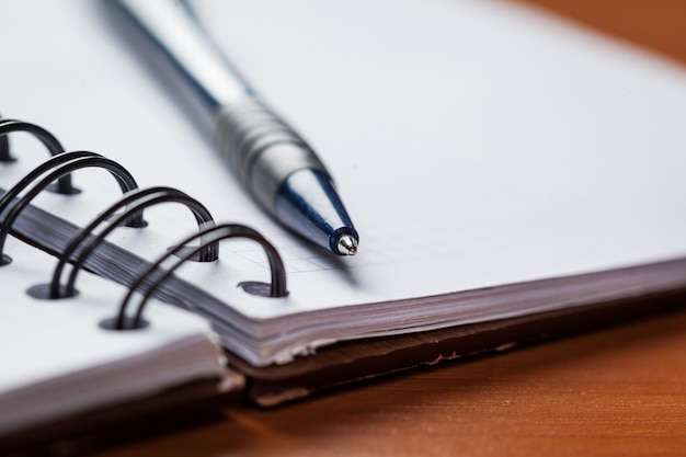 Papel de nota em branco com caneta em madeira fundo