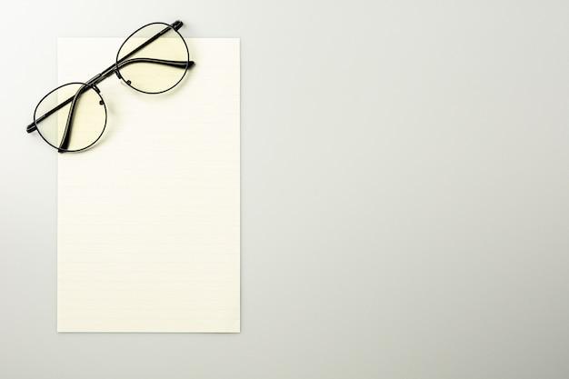 Papel de nota em branco e óculos no fundo da mesa cinza