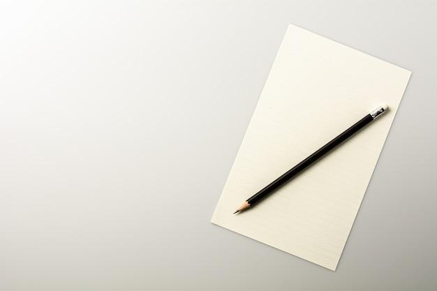 Papel de nota em branco e um lápis na mesa branca.