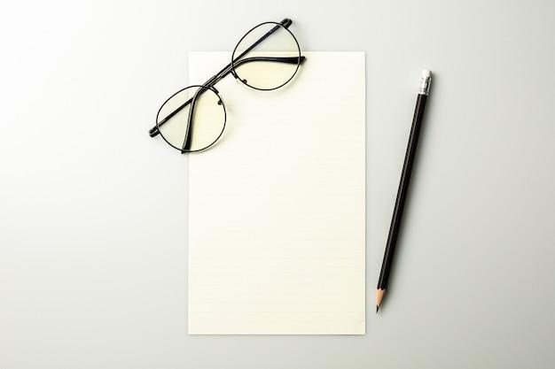 Papel de nota em branco e um lápis na mesa cinza