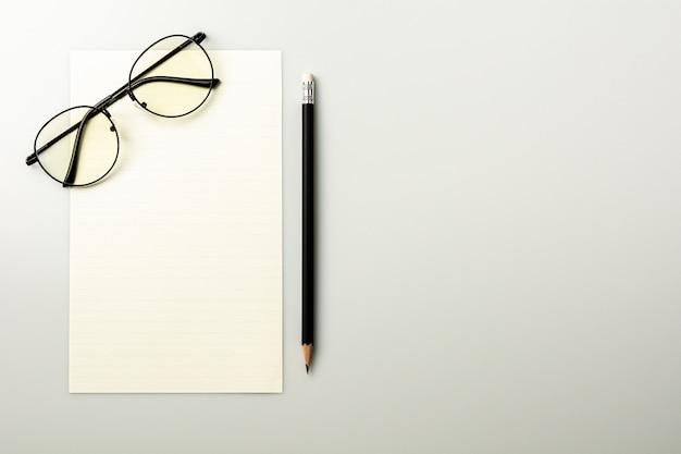 Papel de nota em branco e um lápis no fundo cinzento da mesa.
