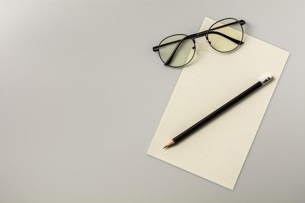 Papel de nota em branco e um lápis no fundo da mesa cinza