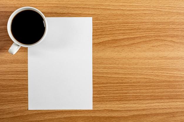 Papel de nota em branco e uma xícara de café na mesa de madeira. - espaço em branco para texto publicitário.