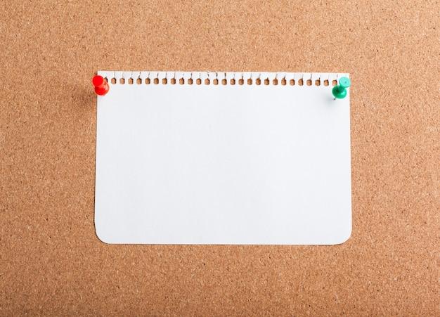 Papel de nota em branco em uma placa de cortiça