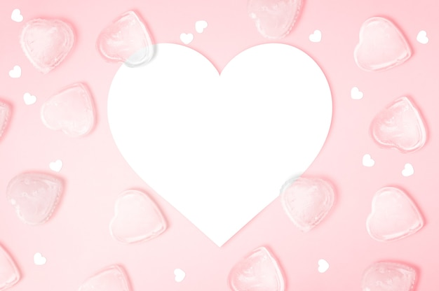 Papel de nota em forma de coração com cubos de gelo de coração em fundo rosa com espaço de cópia, feliz dia dos namorados, dia das mães, plano horizontal, vista de cima