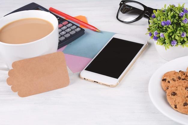 Papel de nota vazia com café, biscoitos e calculadora