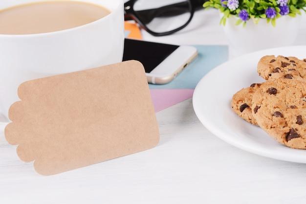 Papel de nota vazia com café, biscoitos e telefone