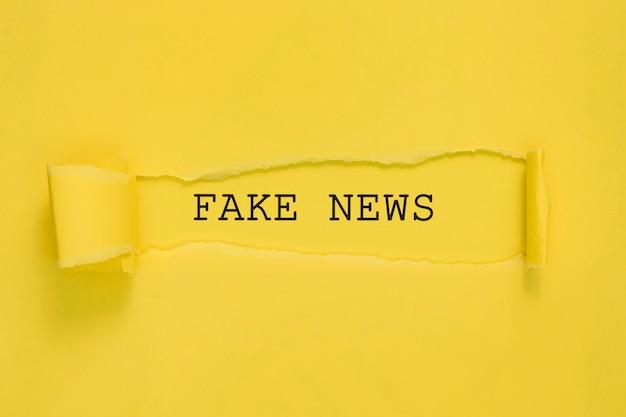 Papel de notícias falsas rasgado na parede amarela