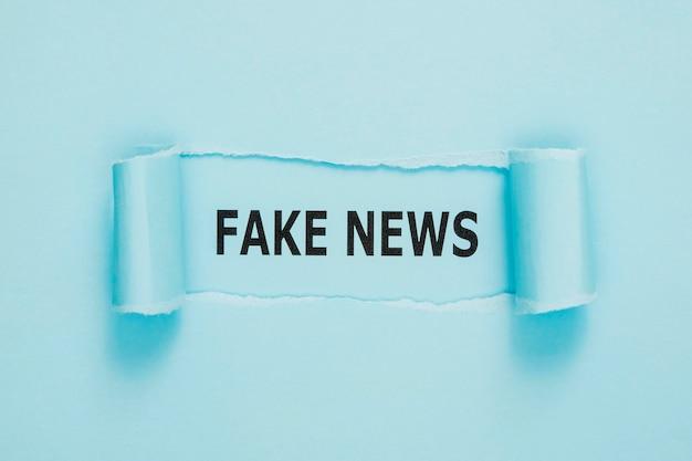 Papel de notícias falsas rasgado na parede azul