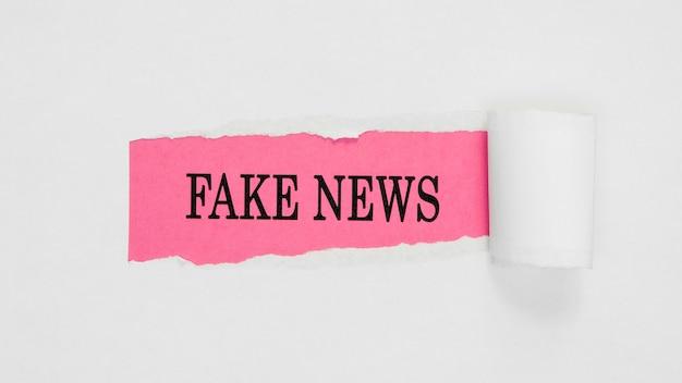 Papel de notícias falsas rasgado na parede rosa e branco