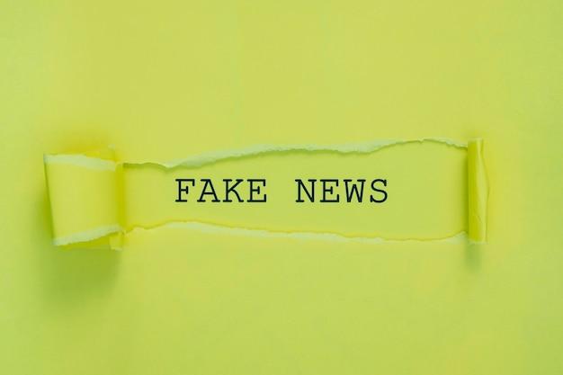 Papel de notícias falsas rasgado na parede verde
