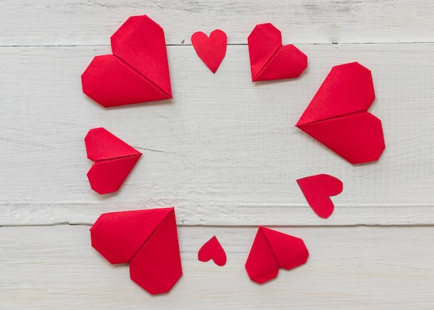 Papel de origami coração vermelho sobre fundo branco woodern, romance e conceito de dia de velentine
