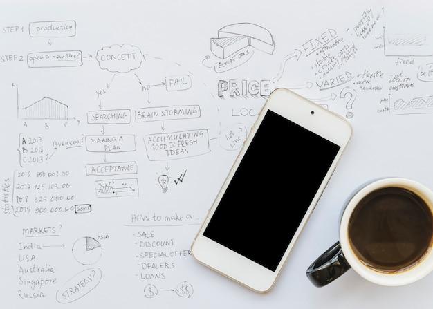 Papel de plano de negócios com xícara de café e smartphone