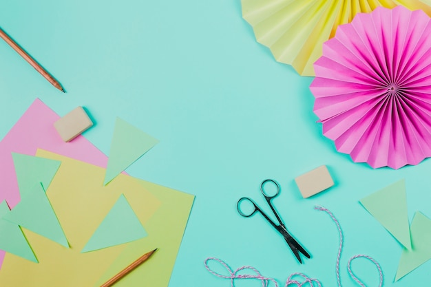 Papel de saudação; lápis; tesoura; papel de flor de borracha e circular no pano de fundo teal