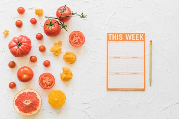 Papel de semana de dieta com lápis e legumes saudáveis em fundo branco
