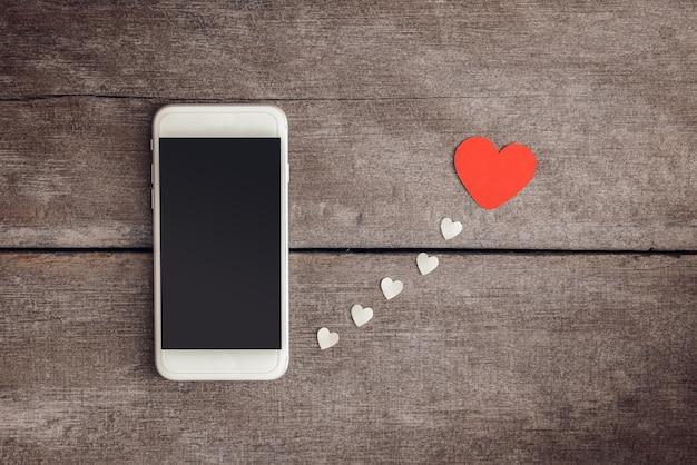 Papel de smartphone e corações em fundo de madeira