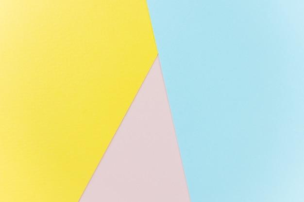 Papel de textura amarelo, rosa e azul.